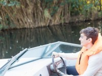 smiling-young-man-behind-the-wheel-of-a-boat_23-2147562075