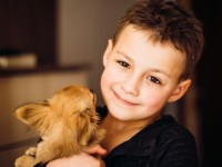 happy-boy-holds-little-dog-standing-in-the-room_1304-3218
